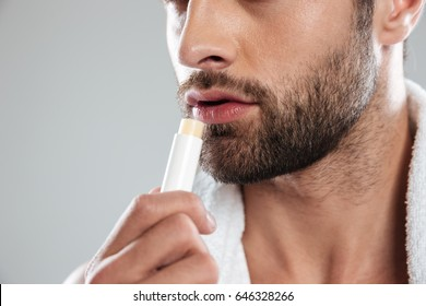 Cropped shot of young bearded man with colorless lipstick isolated