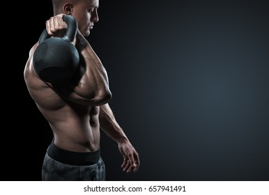 Cropped shot of young bodybuilder holding a kettle bell Strong fitness male exercising crossfit with kettlebell in gym