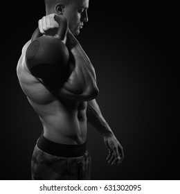 Cropped shot of young bodybulder holding a kettle bell Strong fitness male exercising crossfit with kettlebell in gym
