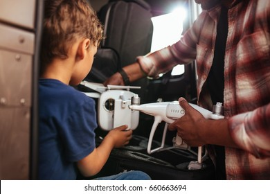 Cropped shot of young boy with father at the back on their car with small drone.
