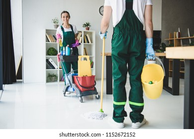 cropped shot of young cleaners holding various cleaning equipment in office