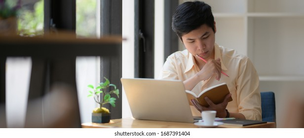 Cropped shot of young college student concentrating on book and laptop to prepare his coming exam