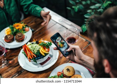 Cropped shot of young couple photographing delicious vegetarian burger and mixed organic salad on white plate in vegetarian restaurant.