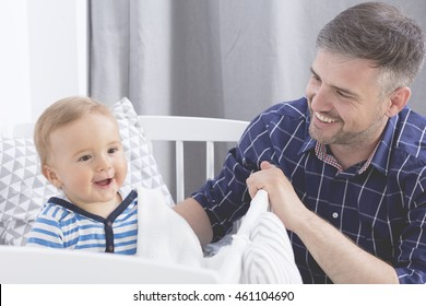 Cropped shot of a young father and his smiling baby in the crib