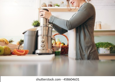 Cropped shot of  young female bar employee making fruit juice using juicer machine at counter.