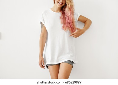 Cropped shot of young female in white oversize T-shirt and jean shorts, having pink hair tips, pointing with finger at copy space, smiling broadly, isolated over white blank wall. Design, advertisment