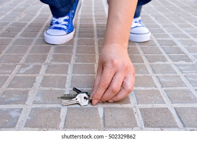cropped shot of a young finding the keys in the street sidewalk