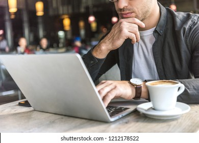 cropped shot of young freelancer working with laptop in cafe with cup of coffee on table
