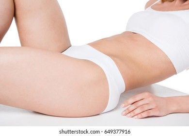 cropped shot of young girl in white underwear lying isolated on white