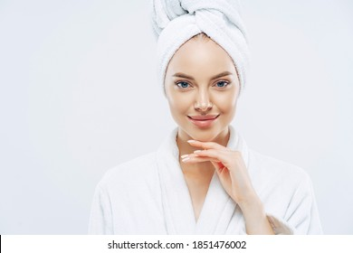 Cropped shot of young good looking European woman looks with calm face, enjoys bath procedures, wears soft white robe, wrapped towel on head, isolated on white background. Morning time, hygiene