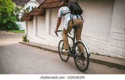 Cropped shot of young handsome hipster male with curly hair with backpack, ride the bike on the city street for ecological life. Man student bicycling with bycicle to the college. People, lifestyle