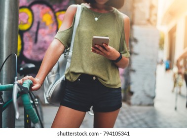 Cropped shot of young hipster student girl walking in the urban streets with bike using smartphone for navigate, attractive woman chatting with friends at social networks via cellphone device