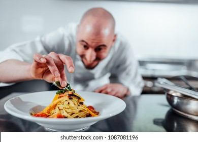 Cropped shot of a young male chef garnishing food in a professional kitchen
