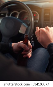 Cropped shot of young man driving a car and drinking alcohol. Transportation and vehicle safety.