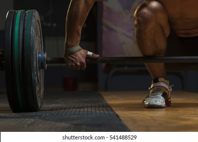 Cropped shot of young muscular man lifting barbell in gym. Weightlifting, power lifting equipment. Sports, fitness - healthy lifestyle concept.