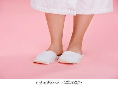 cropped shot of young overweight woman in white slippers and bathrobe  standing on pink 779c70476