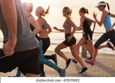 Cropped shot of young people running at sunset. Group of men and women training outdoors for marathon race.