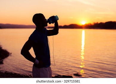 Cropped shot of a young runner silhouette standing on the river bank at sunset and drinking water. Warm sunset tones.