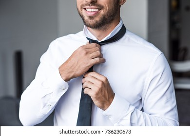 Cropped shot of young smiling businessman putting on a black tie