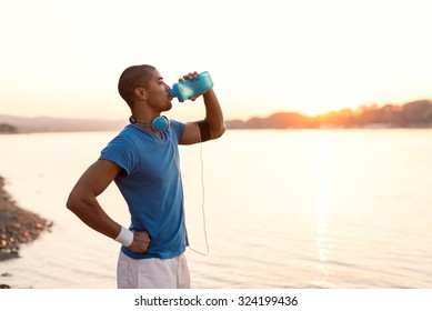 Cropped shot of a young sportsman drinking water while running on riverbank. Warm sunset tones.