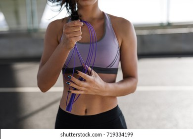 Cropped shot of young sporty woman holding skipping rope