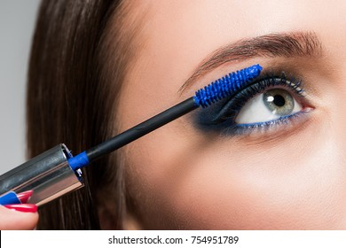 cropped shot of young woman doing eyelashes makeup with blue brush