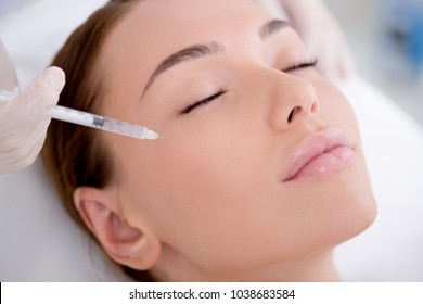 cropped shot of young woman getting beauty injection made by cosmetologist in salon
