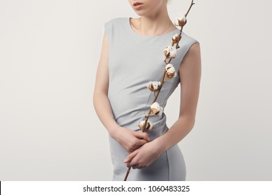 cropped shot of young woman in grey dress with cotton branch isolated on white