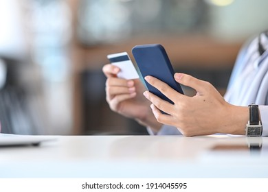 Cropped shot of young woman holding smart phone and credit card for shopping online.