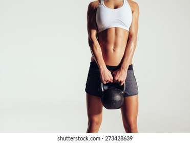 Cropped shot of young woman in sportswear holding a kettle bell. Strong fitness female exercising crossfit with kettlebell in studio. Female model with muscular and slim body on grey background.