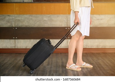 Cropped shot of young woman with suitcase walking to the hotel lobby for check-in her room. Conceptual of tourist when arrival at hotel.