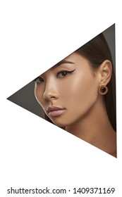 Cropped side geometric portrait of Asian lady with black flicks. The girl with dark hair is wearing blown stud earrings in the shape of flat ring, looking at the camera behind triangle foreground.