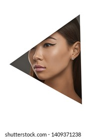 Cropped side geometric portrait of Asian girl with black flicks. The woman with dark hair is wearing square-shaped stud earrings with marbled insert, looking to the side behind triangle foreground.