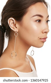 Cropped side half-turn portrait of Asian woman with painted rim of ear, wearing achsel shirt, looking directly. The lady with mole is wearing silver dangle earrings, adorned with ring-shaped pendant.