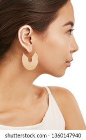 Cropped side half-turn portrait of Asian girl with painted rim of ear, wearing white achsel shirt. The woman with dark hair is wearing long dangle earrings, adorned with beige semioval insertion.