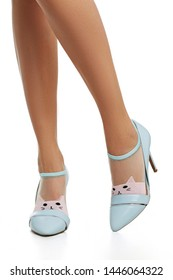 Cropped side shot of female legs in nylon socks, adorned with powder-pink knitted cat's face insertion on toes. The lady is wearing high-heeled light blue shoes, posing against the white background.