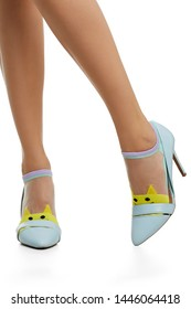 Cropped side shot of female legs in nylon socks, adorned with bright yellow knitted cat's face insertion on the toes. The lady is wearing high-heeled light blue shoes, posing on the white background.