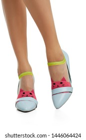 Cropped side shot of female legs in nylon socks, adorned with raspberry red knitted cat's face insertion on toes. The lady is wearing high-heeled light blue shoes, posing on the white background.