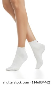 Cropped side view of beautiful female legs in white socks, isolated against a white background. The young woman walking on her tip-toes. Comfortable legwear for ladies and girls. Cozy women's hosiery.