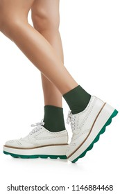 Cropped side view of lean woman's legs in green ankle high socks and thick-soled running shoes, isolated over a white background. Trendy hosiery and footwear for ladies and girls. Clothing for sports.