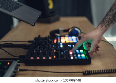 Cropped and side view photo with tattoo hands of DJ master man. He press color button on controller and making music in black modern and sound studio with style interior