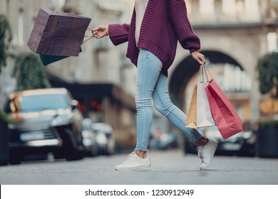 Cropped side view portrait of stylish girl carrying colorful shopping bags