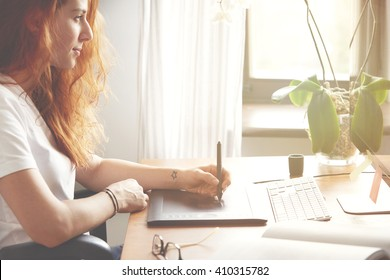 Cropped side view portrait of young female photographer retouching photos on graphic tablet in front of PC while working at home. Redhead woman drawing on digital tablet. Flare sun, film effect