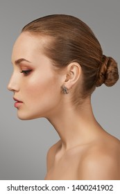 Cropped side view shot of woman with chestnut hair, tied back in a bun, with naked chest and fresh makeup, looking down. The girl with tanned skin is wearing silver earring in the shape of Pegasus.