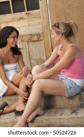 Cropped side view of two young women sitting on an outside porch and talking. They are smiling at each other. Vertical format.