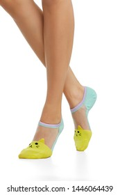 Cropped side view of woman's legs wearing nylon low-cut socks, adorned with bright yellow knitted cat's face insertion on the toes. The woman is standing on her tip-toe, posing on white background.