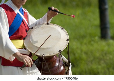 A cropped, side-view of a Korean drummer playing the traditional hourglass-shaped drum (janggu).