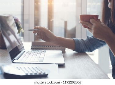 Cropped, smart asian business woman relaxed working on laptop computer and drinking coffee in modern office near the window with calculator and business report on office desk