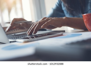 Cropped, smart businesswoman, accountant, entrepreneur working on laptop computer in modern office with smartphone, cup of coffee, calculator and business data report on desk, close up