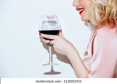 Cropped smiling blonde woman holding a glass of red wine.
